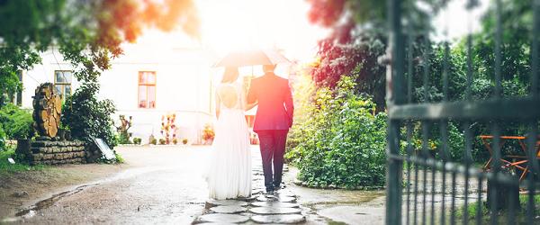A couple walking under a wedding umbrella