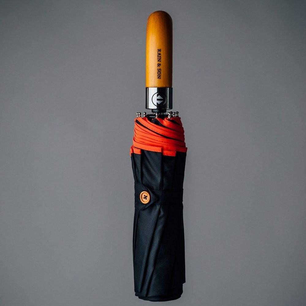 a black umbrella with red reflexion